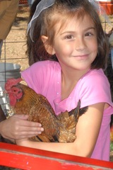 Child cuddling with a hen